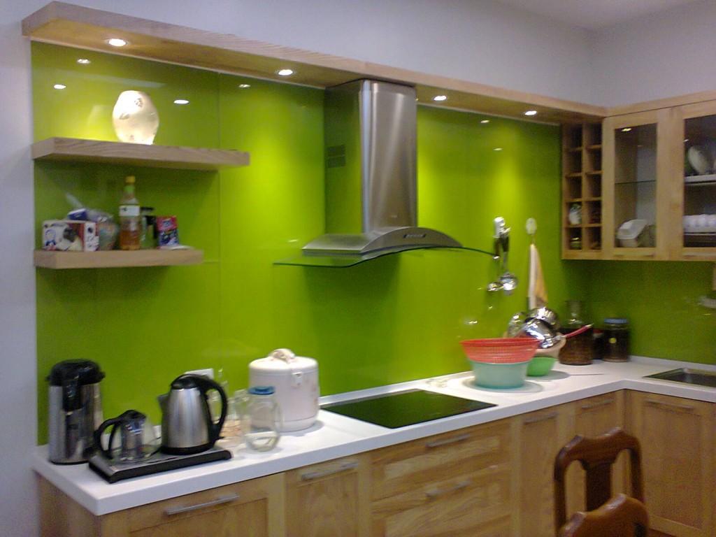 Mẫu 2 : Kính ốp bếp màu xanh non kết hợp bàn đá trắng.