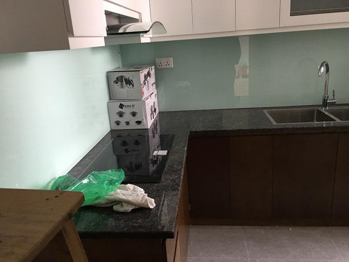 Kính ốp bếp màu trắng xanh kết hợp bàn đá đen tủ bếp trắng.