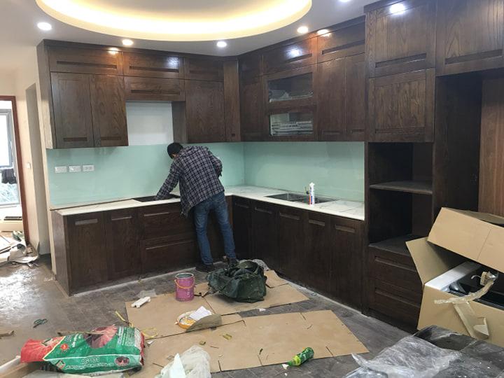 Kính ốp bếp màu trắng xanh kết hợp bàn đá trắng tủ bếp màu gỗ tối.