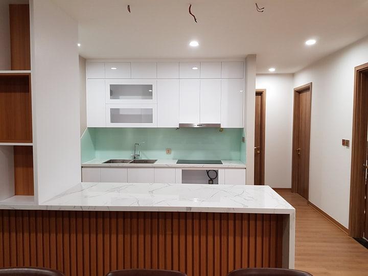 Kính ốp bếp màu trắng xanh kết hợp bàn đá trắng tủ bếp trắng.