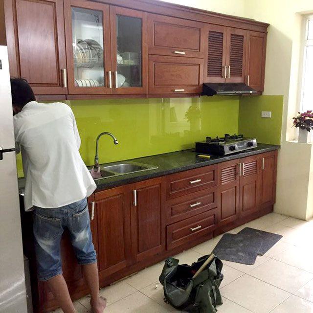 Kính óp bếp màu vàng chanh kết hợp bàn đá đen tủ vân gỗ thịt.
