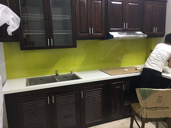 Kính ốp bếp màu vàng chanh kết hợp bàn đá trắng tủ bếp màu gỗ ngụ.