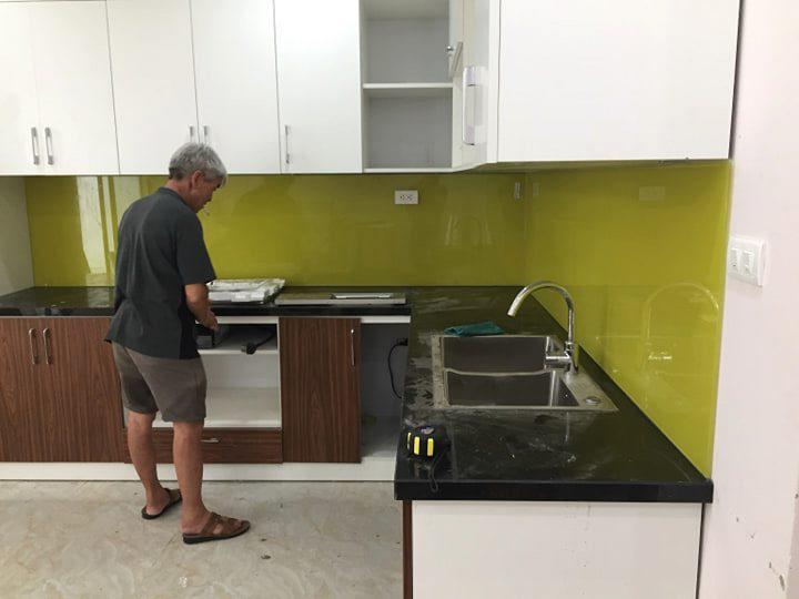 Kính ốp bếp màu  vàng chanh kết bàn đá đen tủ bếp màu trắng.