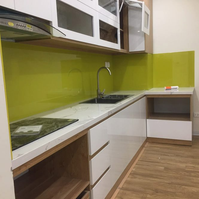 Kính ốp bếp màu vàng chanh kết hợp bàn đá trắng, tủ trắng.